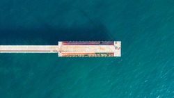 Aerial top view of old pier. View from the flight to a pier with a lighthouse on a sunny day. wooden pier with ocean water, marina. Screensaver on your desktop.
