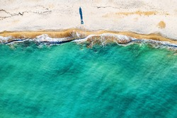 Aerial top view of single human figure casting shadow on sandy beach, standing by sea with beautiful azure tropical sea water and waves, copy space for your text