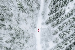 Aerial top view of snow covered forest with winter road and red car. Drone photography landscape.