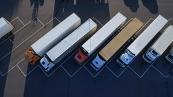 Aerial Top View of White Semi Truck with Cargo Trailer Parking with Other Trucks on Special Parking Lot.