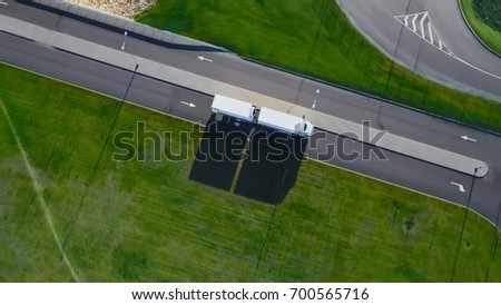 Aerial Top View of White Truck with Cargo Semi Trailer Moving on the Road in the Direction of Loading Warehouse Area.