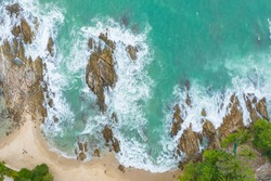 Aerial top view of white waves in green sea hit on the large rocks in summer day. Beach sea space area. green sea, waves crashing on the rocks. At Kalim Beach Phuket Thailand.