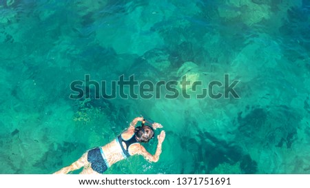 Aerial top view of woman snorkeling from above, girl snorkeler swimming in a clear tropical sea water with corals during summer vacation in Thailand #1371751691