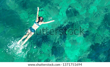 Aerial top view of woman snorkeling from above, girl snorkeler swimming in a clear tropical sea water with corals during summer vacation in Thailand #1371751694