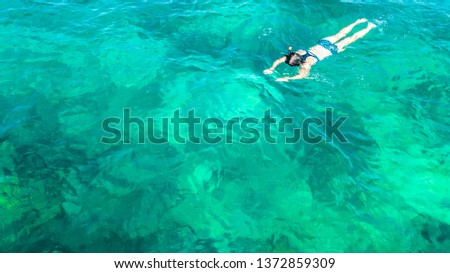 Aerial top view of woman snorkeling from above, girl snorkeler swimming in a clear tropical sea water with corals during summer vacation in Thailand #1372859309