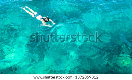 Aerial top view of woman snorkeling from above, girl snorkeler swimming in a clear tropical sea water with corals during summer vacation in Thailand #1372859312