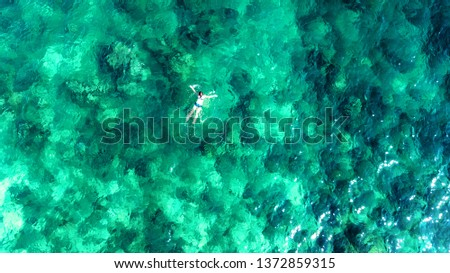 Aerial top view of woman snorkeling from above, girl snorkeler swimming in a clear tropical sea water with corals during summer vacation in Thailand #1372859315