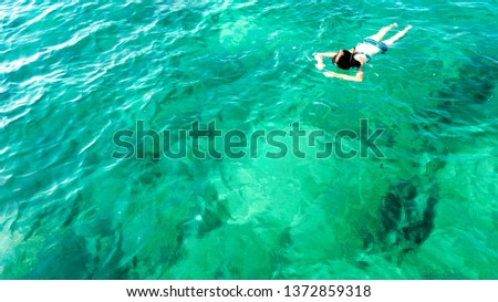 Aerial top view of woman snorkeling from above, girl snorkeler swimming in a clear tropical sea water with corals during summer vacation in Thailand #1372859318