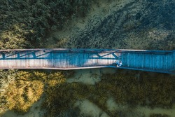 Aerial top view of wooden bridge pathway over marshy river, summer travel concept.