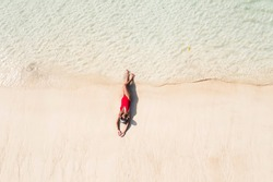 Aerial top view of young woman in red swimsuit and Relaxed  lying on sand during summer vacation which under the sun tanning in a tropical beach