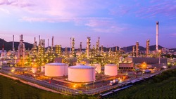Aerial top view oil and gas tank with oil refinery background at night, Business petrochemical industrial, Refinery factory oil storage tank and pipeline,  Ecosystem and healthy environment concepts.