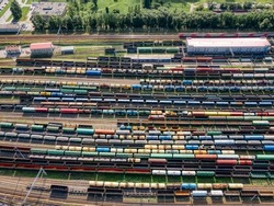 Aerial top view on railway terminal with various colorful cargo wagons. Transportation of various goods by rail. Import and export logistics. Industrial landscape. Freight sorting station.
