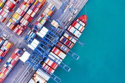 Aerial top view over international container cargo ship at industrial import-export port prepare to load containers with big container loader ship vessel. global transportation and logistic business.
