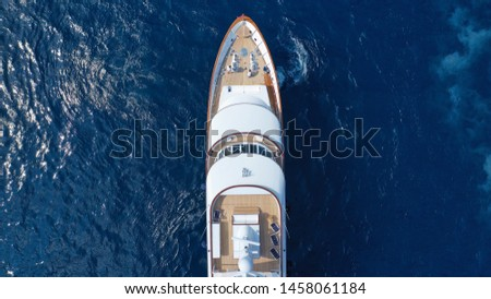 Aerial top view photo of luxury yacht with wooden deck docked in deep blue open ocean sea stock photo