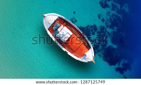 Aerial top view photo of red traditional wooden fishing boat in Aegean island destination  port with turquoise sea