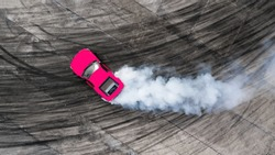 Aerial top view professional driver drifting car on asphalt road track with white smoke, Automobile race car drift on abstract asphalt road with black tire skid mark, View from above.