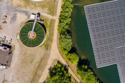 Aerial top view solar power station float the pond near recirculation sedimentation tank, water treatment plant