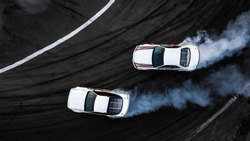 Aerial top view two car drift battle on asphalt race track, Automobile and automotive car view from above, Professional car drifting, Race drift car with white smoke from burning tires on speed track.