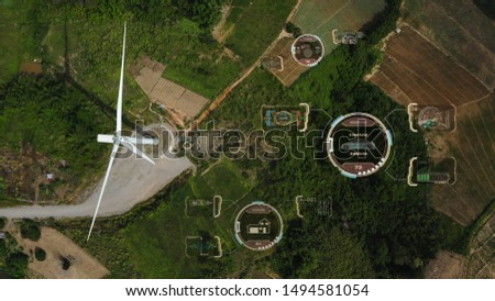 Aerial top view, windmills with digitally generated holographic display tech data visualization. Wind power turbines generating clean renewable energy for sustainable development in green ecologic way #1494581054