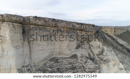 Aerial top viewfor breathtaking white cliff near green valley on beautiful, cloudy sky background. Shot. White, high rock cliff near the field with green grass. #1282975549