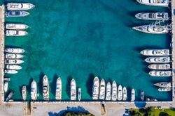 Aerial topdown view to a marina with moored luxury yachts and sailing boats and copy space in the middle