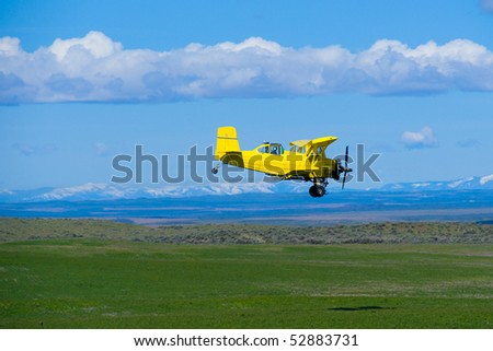 Aerial topdresser agricultural aircraft spraying fertilizer over green field