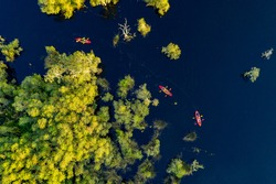 Aerial topview of tourists playing adventure activity sport for paddling kayak or canoe on the lake with the trees in Rayong Botanical Garden national park in Thailand