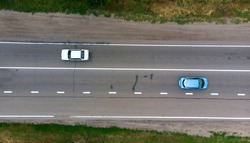 Aerial. Two sedan cars driving by the highway. Top view from drone.