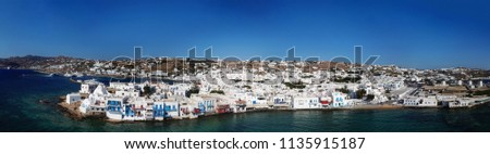 Aerial ultra wide panoramic drone view of iconic chora of Mykonos island featuring picturesque little Venice, Cyclades, Aegean, Greece