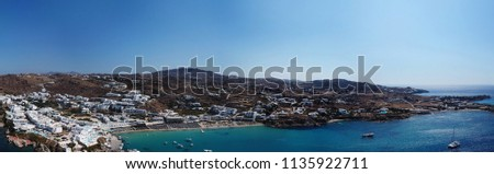Aerial ultra wide panoramic drone view of iconic turquoise clear water beach of Platy Gialos with yachts docked, Mykonos island, Cyclades, Aegean, Greece