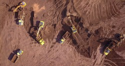 Aerial: Vast excavation site with multiple heavy industry vehicles.