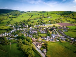 Aerial view above houses, an old British village in the countryside. Warm colours give a homely effect.