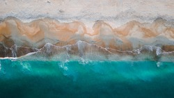 Aerial View Above Sandy Beach Seashore of Clear Blue Aqua Waves Breaking on Shore at Dusk Sunset. Beautiful Ocean coast tropical background texture