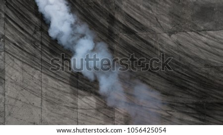 Aerial view abstract background with tire marks and smoke on race track.