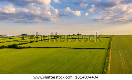 Aerial view across green fields to the horizon and cloudy blue sky over Oxfordshire stock photo