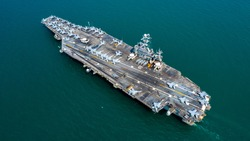 Aerial view America battleship navy nuclear aircraft carrier, USA military navy airplane ship carrier full loading plane fighter jet aircraft, American warship in open ocean, United States of America.