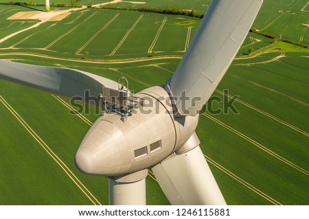 Aerial view and closeup of a wind turbine in a wind farm