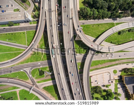 Aerial view at junctions of city highway. Vehicles drive on roads. Russia