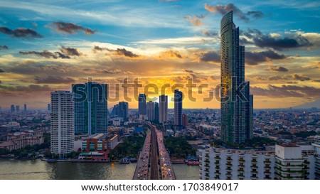 Aerial view Bangkok City skyline and skyscraper on Sathorn Road business and financial in Bangkok downtown, Taksin Bridge over Chao Phraya River, Bangkok, Thailand at sunset.