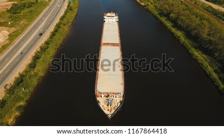Aerial view:Barge with cargo on the river. River, cargo barge, highway with cars.. Cargo ship on the river.