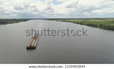 Aerial view:Barge with cargo on the river Volga. River tugboat moves cargo barge, Cargo ship on the river.