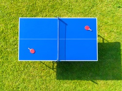 Aerial view blue table tennis or ping pong. Close-up ping-pong net. Close up ping pong net and line. Top view two table tennis or ping pong rackets or paddles  and ball on a blue table with net