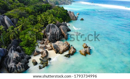 Aerial view by a drone of Anse Source d'Argent, La Digue Seychelles. Two people standing on a perfekt beach with a turquoise ocean and giant rocks in the background Photo stock ©