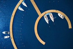 Aerial View by Drone of Yacht Club and Marina. Top view of yacht club. White boats in sea water. Marina dock yachts and small motor boats. Yacht and sailboat is moored at the quay. Parking