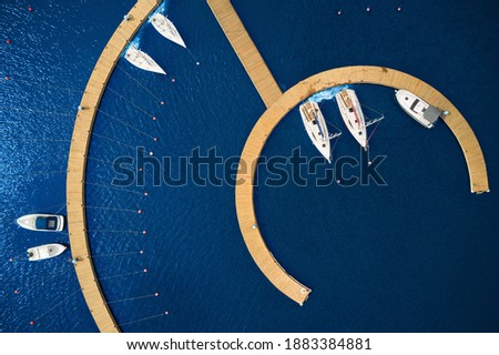 Aerial View by Drone of Yacht Club and Marina. Top view of yacht club. White boats in sea water. Marina dock yachts and small motor boats. Yacht and sailboat is moored at the quay. Parking Stock fotó ©