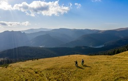 Aerial view. Epic shot of two mountain bikers on top of the mountain looking down the valley. Aerial shot of mountain biker on the top looking at amazing view in the autumn. mountain bike. bycicle