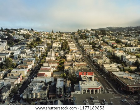 Aerial view Eureka Valley neighborhood with rolling hills cityscape, typical Victorian houses. Castro District is synonymous with gay culture, tightly packed residential homes under summer foggy