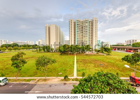 Aerial view exterior public housing HDB resident buildings, new multistory flats complex with grass courtyard, trees, pedestrian path, dense of apartments at sunset in Eunos neighborhood, Singapore. #544572703