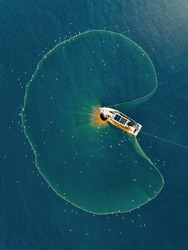 Aerial view fisherman catching fish using net at the ocean.