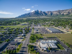 Aerial view from a drone of Washington Blvd and the commercial district of North Ogden, Utah with Ben Lomond Peak and the Wasatch Mountains visible in the background